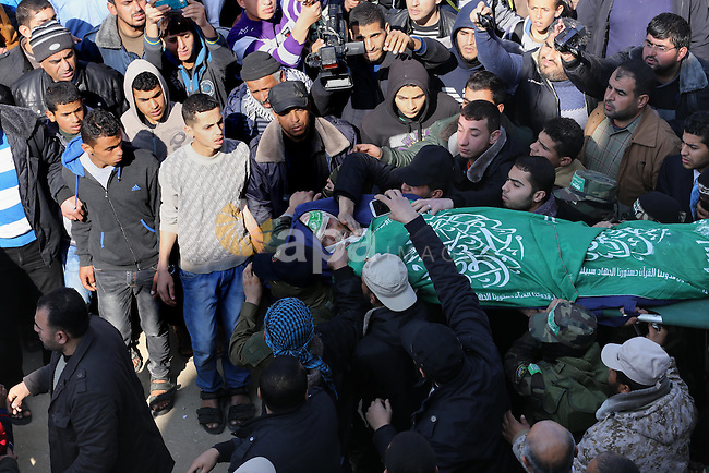 Palestinian militants carry the body of their comrade Fuad Abu Atewi, who was killed when a tunnel collapse on Tuesday, during his funeral in the village of Al-Moghraga near the Nuseirat refugee camp in the central Gaza Strip on February 3, 2016. The collapse of a tunnel in the Gaza Strip has killed two militants from Hamas's armed wing, officials said Wednesday, as concern grows in Israel over the rebuilding of tunnels that can be used for attacks. Photo by Mohammed Asad