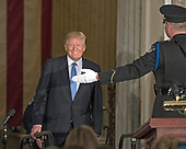 United States President Donald J. Trump is directed to his seat by a US Capitol Police officer as he arrives to attend a Congressional Gold Medal ceremony honoring former US Senator Bob Dole (Republican of Kansas) in the Rotunda of the US Capitol on Wednesday, January 17, 2017.  Congress commissioned gold medals as its highest expression of national appreciation for distinguished achievements and contributions.  Dole served in Congress from 1961 through 1996, was the Senate GOP leader from 1985 through 1996, and was the 1996 Republican Party nominee for President of the United States.<br /> Credit: Ron Sachs / CNP