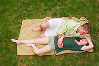 Young couple relaxing on blaket in the grass