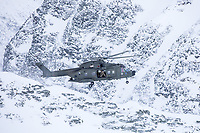 A British Merlin helicopter fly over a mountain ridge during practice in the Arctic, near Bardufoss, Norway. <br /> <br /> In 2019 the Arctic exercise Clockwork passed 50 years of training in Norway, and now has a permanent base within the Norwegian Air Force base at Bardufoss. <br /> <br /> 845 Naval Air Squadron is a squadron of the Royal Navy's Fleet Air Arm. Part of the Commando Helicopter Force, it is a specialist amphibious unit operating the Leonardo Commando Merlin Mk3 helicopter and provides troop transport and load lifting support to 3 Commando Brigade Royal Marines.<br /> <br /> &copy;Fredrik Naumann/Felix Features