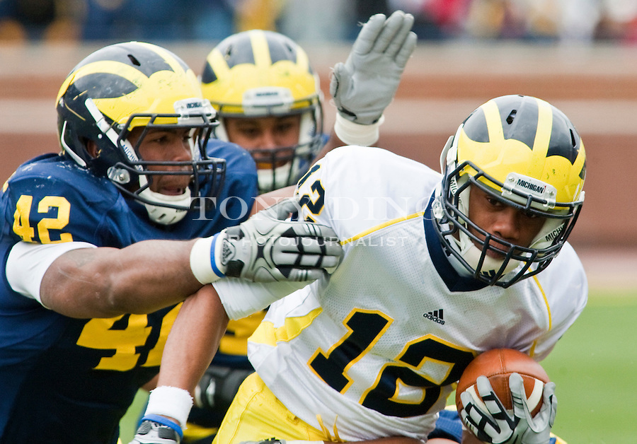 Michigan linebacker J.B. Fitzgerald (42) tries to stop wide receiver Roy Roundtree (12) during the Wolverines' spring football game, Saturday, April 17, 2010, in Ann Arbor, Mich. (AP Photo/Tony Ding)