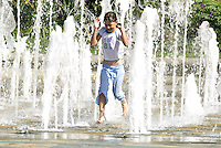 A young girl runs through the Goodwin Fountain in the Peace Gardens in Sheffield, South Yorkshire
