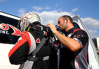 Aug. 16, 2013; Brainerd, MN, USA: Crew member helps NHRA top fuel dragster driver Steve Torrence during qualifying for the Lucas Oil Nationals at Brainerd International Raceway. Mandatory Credit: Mark J. Rebilas-