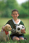 portrait of smiling girl in uniform holding soccer ball and puppy