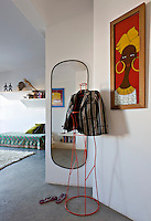 A jacket is draped on a metal frame in front of a wall-mounted mirror in the bedroom.