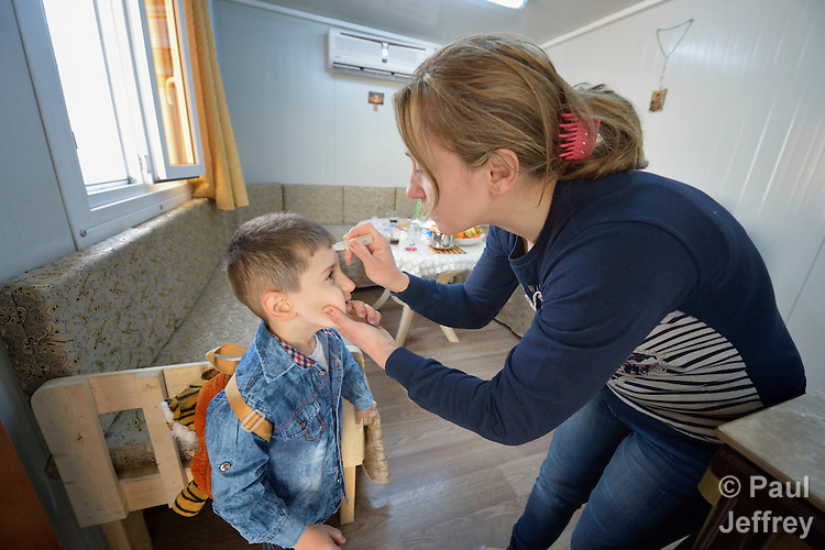 Every morning in Ankawa, Iraq, as her 4-year old son Luis prepares to leave for preschool, Raeda Firas takes a stick of oil and makes the sign of the cross on his forehead. <br /> <br /> The Christian family was displaced from Mosul by ISIS in 2014, and lives in a church-provided modular home.