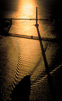 aerial photograph of a the silhouette and shadow of the Golden Gate bridge at sunset with the wake of a containership that just passed under the bridge, San Francisco, California
