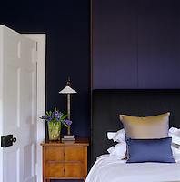 A vase filled with hyacinths stands on the bedside table in this rich purple bedroom