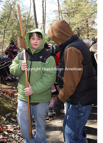 Sean Chilson help to carry the cross along with dozens of Good Friday observers who gathered to celebrate the Way of the Cross service at Shrine of Lourdes in Litchfield Friday morning. Stations depicting the crucifixion and resurrection of Jesus are positioned along a paved path in the woods on the Shrine's grounds. . Michael Kabelka / Republican-American