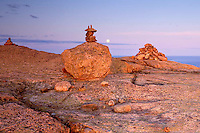 Stone ahus mark the trail at the top of Cadillac Mountain as a full moon rises over the Atlantic Ocean.