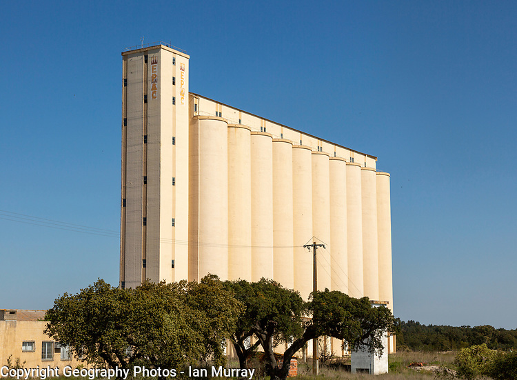 Large EPAC grain cereal silo in arable farming area standing tall against deep blue sky, near Pavia, Alentejo, Portugal southern Europe