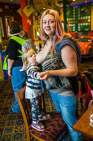 A mother breastfeeds her two year old daughter with her twelve week old baby asleep in a sling on her back.in the family restaurant and play area of a pub. The mother is standing and the boy is feeding while standing on a chair.<br /> <br /> Lancashire, England, UK<br /> <br /> Date Taken:<br /> 07-01-2015<br /> <br /> &copy; Paul Carter / wdiip.co.uk