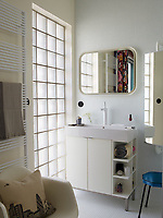 In the tiled bathroom, the radiator towel rail is by Italian manufacturer Tubes. The cabinet and mirror are from Ikea and the stool is a flea market find.  The hand basin is set on top of a storage unit. A window of opaque glass blocks allows a soft light into the room.