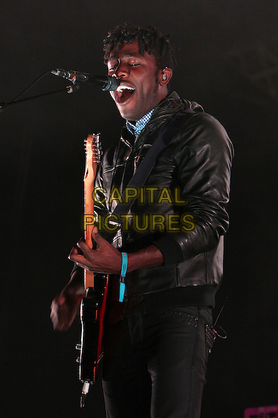 BLOC PARTY - Kele Okereke.Live at the Grand Hall, Olympia, Kensington, London, England..April 11th, 2009.stage concert gig performance music half length guitar singing jacket black leather .CAP/MAR.© Martin Harris/Capital Pictures.