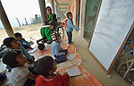 A girl reads aloud from a whiteboard in a class in Pida, a village in Nepal's Dhading District where the United Methodist Committee on Relief (UMCOR), a member of the ACT Alliance, is helping families to rebuild their lives in the wake of the 2015 earthquake that ravaged much of Nepal. UMCOR is constructing new classrooms to replace quake-damaged buildings, but in the meantime classes meet outside the old buildings.