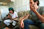 A settler listens to his friend playing guitar in the container they live in, at the unauthorized Israeli outpost of Tekoa D, West Bank.