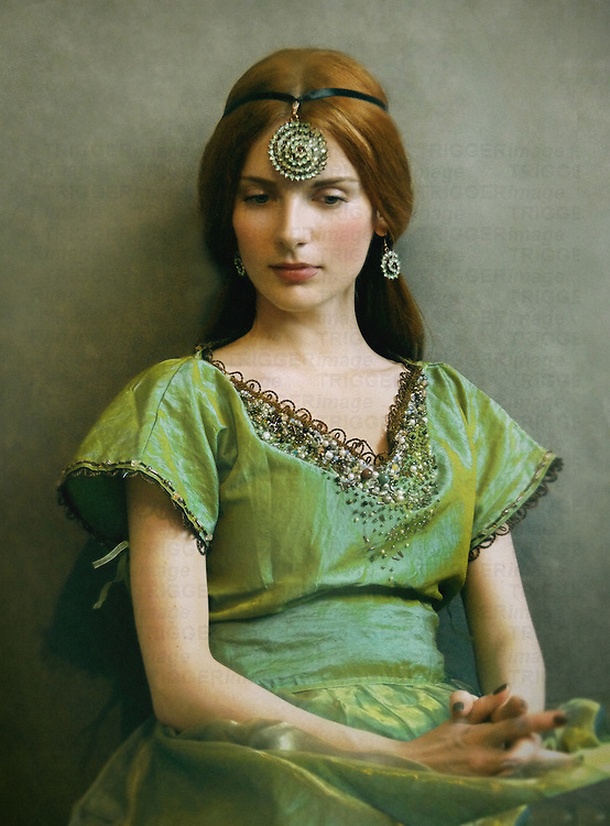 A woman with red hair, seated by a wall, wearing a large rhinestone necklace/headdress and a vintage green tafeta gown.