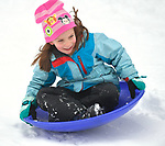 Johanna Hartin, 6, of Belleville slides down a slope at East End Park in Belleville on Saturday morning January 12, 2019. She was there with parents Brennan and Gina Hartin. People were busy digging out -- and some were having fun -- after a major snowstorm hit the St. Louis metropolitan region. <br /> Photo by Tim Vizer