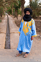 Merzouga, Morocco.  Amazigh Berber Young Man and Irrigation Canal Carrying Water to Farmers' Plots in the Merzouga Oasis.