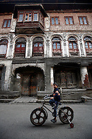 A  lone boy on bicycle in a back street as paramilitary police enforce a curfew imposed to stop separists gather for a political demonstration in Srinagar. Typical building of the old city in the background. Kashmir, India. © Fredrik Naumann/Felix Features