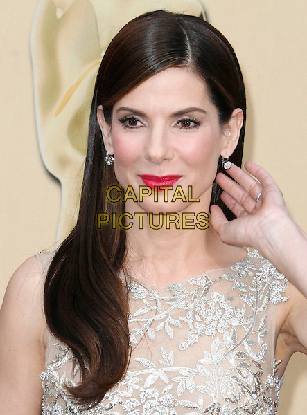 SANDRA BULLOCK.The 82nd Annual Academy Awards held aat The Kodak Theatre in Hollywood, California, USA..March 7th, 2010.oscars headshot portrait silver gold beige beads beaded pink lipstick hand.CAP/EAST.©Eastman/Capital Pictures.