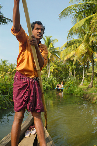 Indian boatman punting boat with tourists through the small canals of the backwaters in Kerala, India.