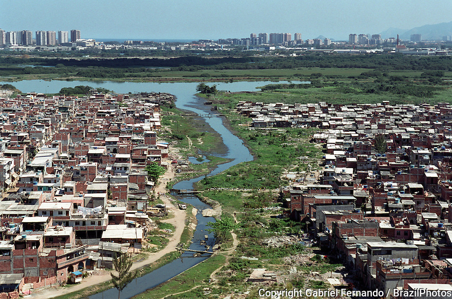 Rio das Pedras slum, Rio de Janeiro, Brazil. River used as open sewer. Lack of wastewater treatment services. Housing conditions in shantytown, poverty. Contrast with medium-class apartment buildings.