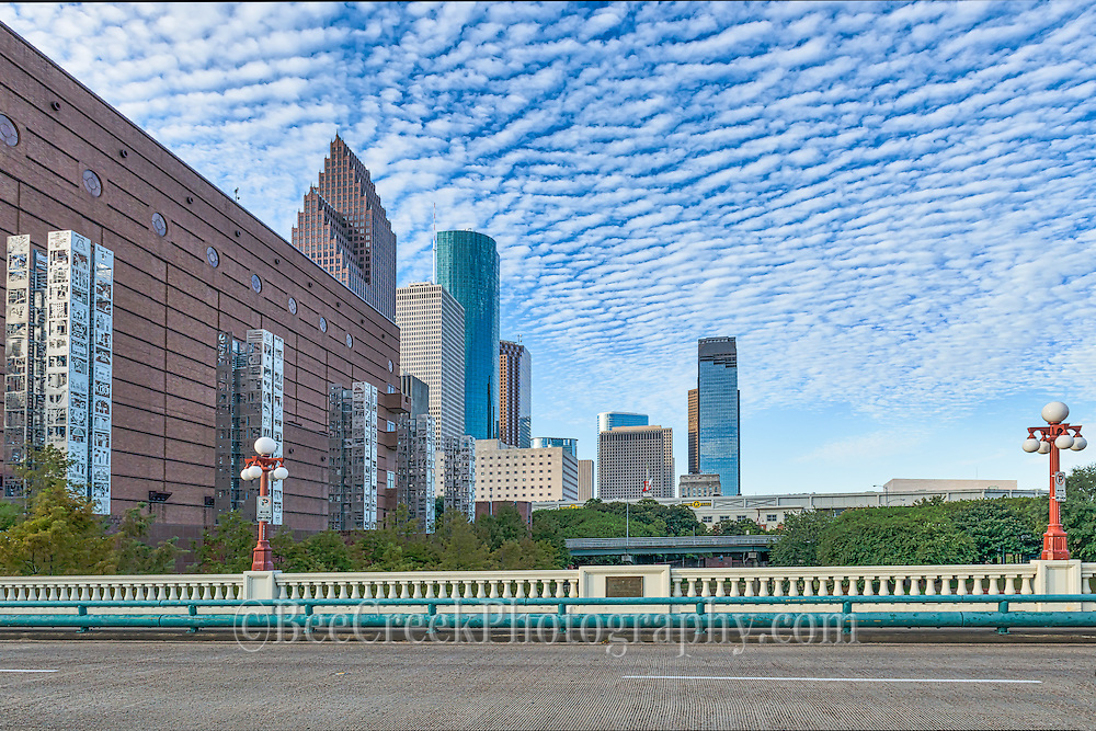 This is another view of the seven wonder art exhibit along with the Houston skyline that run along side the Wortham Center in the Art District cityscape from the Preston Avenue Bridge view.  This is five of seven wonders art exhibits statues located in the theater district in downtown Houston along the side of the Wortham Art Center. They sky were looking very nice this morning with the clouds and blue sky as a back drop to the cityscape. To see these sculptures they are easliy seen from the Preston Avenue Bridge and are 70 feet tall sculptures sitting on 30 feet pillars which were design to represent the city history agriculture, energy, manufacturing, medicine, philanthropy, technology and transportation.  Each column has 150 etching in steel of 1,050 children drawings who were born in 1986 which was 150 years sesquicentennial year. By day these column have a look of shiny lace which is really laser cut steel and at night they glow from within like a lantern along the wall of the Wortham Theater the home of the Houston Opera and ballet. Watermark will not appear on image