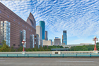Houston Seven Wonders Art -  This is another view of the seven wonder art exhibit along with the Houston skyline that run along side the Wortham Center in the Art District cityscape from the Preston Avenue Bridge view.  This is five of seven wonders art exhibits statues located in the theater district in downtown Houston along the side of the Wortham Art Center. They sky were looking very nice this morning with the clouds and blue sky as a back drop to the cityscape. To see these sculptures they are easliy seen from the Preston Avenue Bridge and are 70 feet tall sculptures sitting on 30 feet pillars which were design to represent the city history agriculture, energy, manufacturing, medicine, philanthropy, technology and transportation.  Each column has 150 etching in steel of 1,050 children drawings who were born in 1986 which was 150 years sesquicentennial year. By day these column have a look of shiny lace which is really laser cut steel and at night they glow from within like a lantern along the wall of the Wortham Theater the home of the Houston Opera and ballet. Watermark will not appear on image