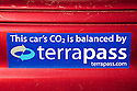 A close up of bumper sticker on a red car declaring the purchase of carbon offsets for the car's carbon emissions. TerraPass is a carbon offset company serving individuals and businesses. Palo Alto, California, USA