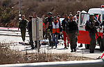 Israeli security forces and emergency personnel stand next to the body of a Palestinian man who was shot dead after allegedly trying to stab Israeli police at the Tapuah junction, south of the West Bank city of Nablus, on October 30, 2015. Two Palestinians allegedly tried to stab Israeli police at the West Bank checkpoint, one of whom was shot dead while the other was wounded by Israeli fire, police said. Photo by Nedal Eshtayah