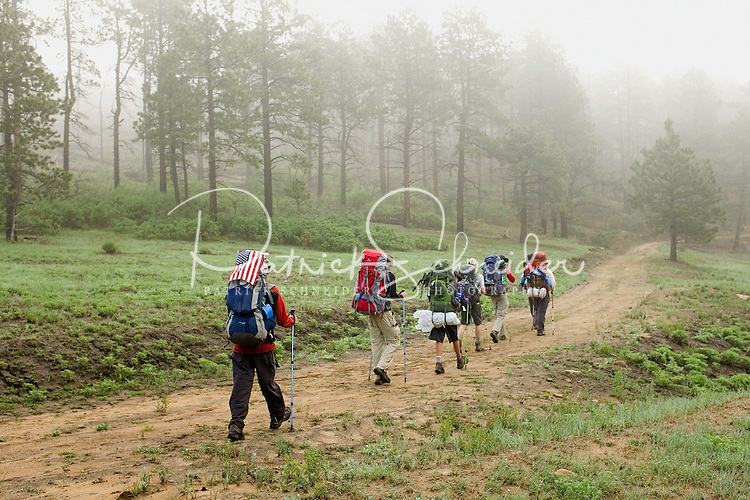 Photo story of Philmont Scout Ranch in Cimarron, New Mexico, taken during a Boy Scout Troop backpack trip in the summer of 2013. Photo is part of a comprehensive picture package which shows in-depth photography of a BSA Ventures crew on a trek.  In this photo a BSA Venture Crew Scouts hike their way through the early morning fog hanging in the wooded backcountry at Philmont Scout Ranch.   <br /> <br /> The  Photo by travel photograph: PatrickschneiderPhoto.com