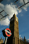 Big Ben against blue sky and white clouds with Underground sign and Perspex roof in foreground London England