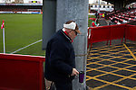 An elderly home fan with carrying a hot drink towards the main stand at Aggborough, home of Kidderminster Harriers before they played visitors Gainsborough Trinity in a National League North fixture. Harriers were formed in 1886 and have played at their current home since 1890. They won this match  by 3-0 watched by a crowd of 1465.