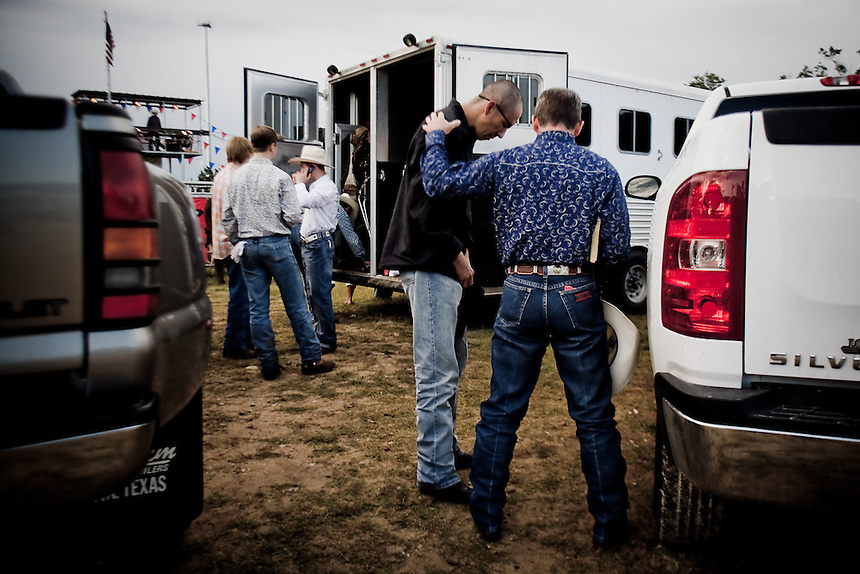 A minister prays with Jimmy 'Stretch' Borunda at a rodeo in Wimberley, Texas. After Stretch lost sight in his left eye he returned to the rodeo arena where he feels most at home with his friends. May 23, 2009.