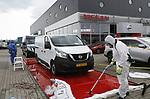 Foto: VidiPhoto<br /> <br /> EDE &ndash; Bij autobedrijf Bochane in Ede is dinsdag begonnen met het opruimen van asbest die zondag bij een bedrijfsbrand vrij kwam. De opruim- en schoonmaakwerkzaamheden op het bedrijventerrein Frankeneng gaan nog zeker tot vrijdag duren. Door de harde wind is de asbest verspreid over een groot gebied. Bij Bochane zelf moeten 200 auto&rsquo;s met de hand gewassen worden. Het afvalwater wordt opgezogen en afgevoerd. Door de opruimwerkzaamheden is een aantal bedrijven in de omgeving lastig bereikbaar. Ondernemers zijn boos dat ze hun eigen bedrijf schoon moeten laten maken. Klanten van Bochane worden zoveel mogelijk omgevangen bij vestigingen in naburige plaatsen. De levering van nieuwe auto&rsquo;s loopt vertraging op omdat ook medewerkers van het bedrijf zelf niet het terrein op mogen. Over de totale schade is nog niets bekend.