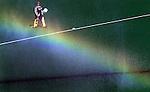 EK Hockey. Oranje trainde donderdag voor de halve finale wedstrijd van vrijdag tegen Belgie. Doelman Ronald Jansen loopt door een regenboog tijdens het sproeien van het veld.