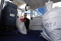 February 16, 2013  Volunteer Iditarod Air Force pilot, Scott Ivany, loads his plane with musher food bags bound for the Rainy Pass checkpoint at the Willow airport as musher food, straw, HEET and people food is flown to the 4 checkpoints on the east side the Alaska Range. ..Iditarod 2013    Photo Copyright Jeff Schultz  -- Do not reproduce without written permission
