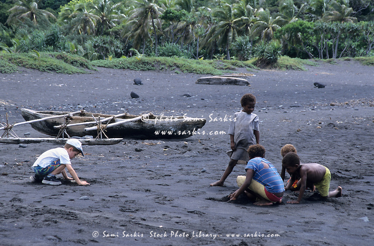 Melanesian children playing on a black sandy beach with a Caucasian boy, Sulphur Bay Village, Ipekel Ipeukel, Tanna Island, Vanuatu.