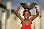 A girl carries a bowl in Batey Bombita, a community in the southwest of the Dominican Republic whose population is composed of Haitian immigrants and their descendents.