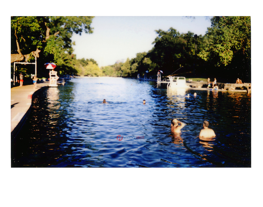 Fujifilm instax instant-film picture of Barton Springs Pool as swimmers enjoy the cool clear water of Spring-feed family friendly recreational outdoor swimming pool - Stock Image.
