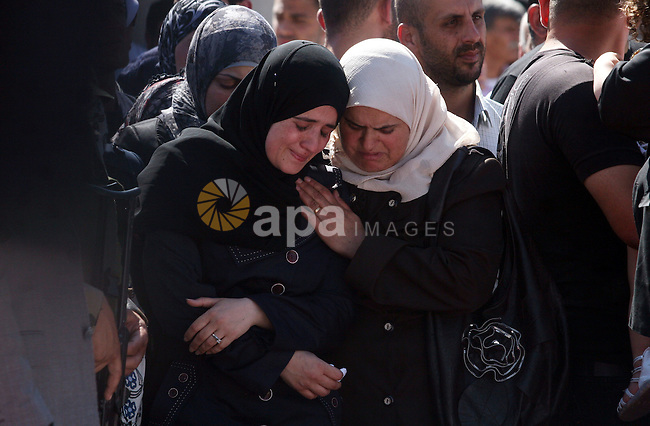 Palestinian women mourn during the funeral of 91 Palestinians whose remains were returned by Israel at the Palestinian headquarters in the West Bank city of Ramallah on May 31, 2012. Israel handed over the remains of scores of Palestinian militants killed in attacks against Israel, a Palestinian official said.   Photo by Issam Rimawi