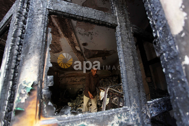A man checks the scene inside the burnt campaign headquarters of candidate and former prime minister Ahmed Shafiq in Cairo May 29, 2012. A group of Egyptian protesters set fire to the headquarters on Monday, the state news agency reported, after the ex-prime minister made it into the second round of the vote. Photo by Ashraf Amra
