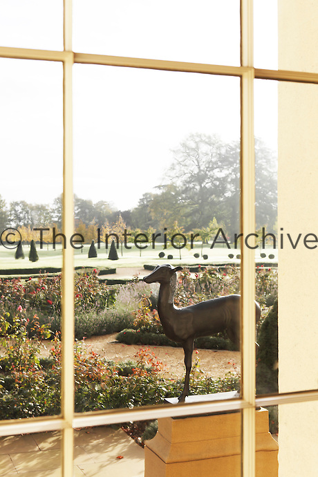 A view from a window onto the rose garden and a sculpture of a deer