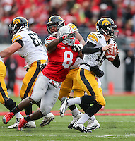 Iowa Hawkeyes quarterback Jake Rudock (15) throws the ball moment before being tackled by Ohio State Buckeyes defensive lineman Noah Spence (8) during Saturday's game in Columbus, Ohio on Saturday, Oct. 19, 2013. (Jabin Botsford / The Columbus Dispatch)