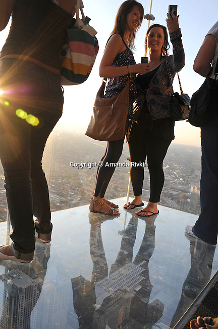 "Visitors take pictures on the newly opened glass balconies ""The Ledge"" at the Skydeck at the Sears Tower in Chicago, Illinois on July 6, 2009."