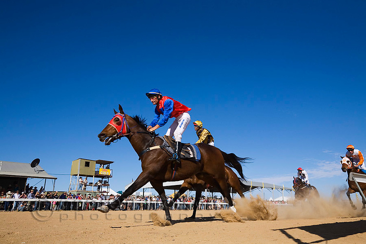 Outback horse racing at the dirt track in Birdsville - during the annual Birdsville Cup Races.  Every September thousands of horse racing enthusiasts arrive in the small outback town for the famous bush carnival.  Birdsville, Queensland, AUSTRALIA.