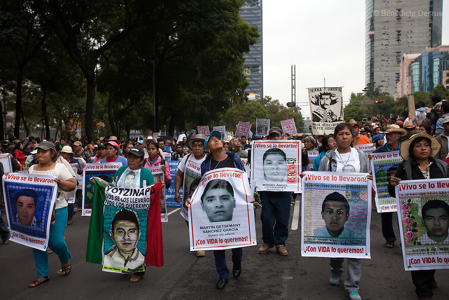 Parents and Relatives of some of the 43 missing students from Mexico's Ayotzinapa College Raul Isidro Burgos hold posters of them during a march to mark the one-year anniversary of their disappearance, in Mexico City, Mexico on September 26, 2015. Families of the missing and international experts cast doubt on Mexican government's official account of the incident: that municipal police handed the students over to a local drug gang who burned their bodies in a nearby garbage dump. The families asked the government to launch a new internationally supervised investigation and to review Mexico's own investigators. More than 25,000 people have disappeared in Mexico since 2007, according to the government. (Photo by Bénédicte Desrus)