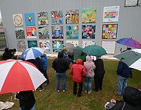 NWA Democrat-Gazette/ANDY SHUPE<br /> A crowd gathers in the rain Saturday, April 13, 2019, during an unveiling ceremony and celebration for The Better World Mural at Terra Studios in Durham. The project features the work of 19 local artists to create panels which together portray the notion of compassion and 17 sustainable development goals held by Terra Studios, Compassion Fayetteville, a group of local businesses and community members.