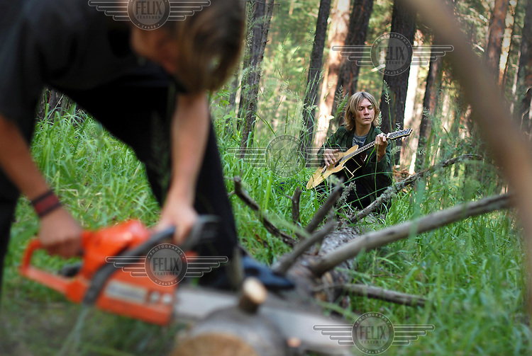 A boy plays a guitar while a man saws a tree in a forest near Abakan, where Father Alexander is leading a summer camp for the children from his Russian Orthodox church.